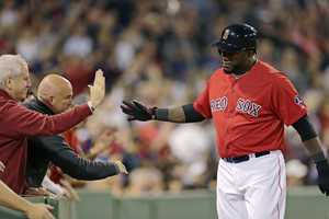Boston Red Sox designated hitter David Ortiz is congratulated by fans after scoring on a hit by David Carp in the seventh inning of a baseball game at Fenway Park, Sept. 20, 2013.