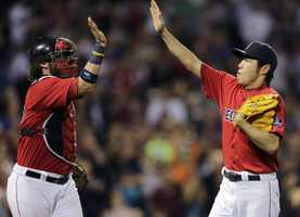 Boston Red Sox relief pitcher Koji Uehara, right, is congratulated by catcher Jarrod Saltalamacchia after striking out Toronto Blue Jays' J.P. Arencibia to end the top of the eighth inning of a baseball game at Fenway Park, Friday, Sept. 20, 2013.