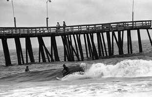 A surfer oblivious to the approaching Hurricane Gloria rides the waves under a fishing pier in Virginia Beach, Virginia on Thursday, Sept. 26, 1985. Gloria, packing 130 mile-per-hour winds, is threatening the east coast.