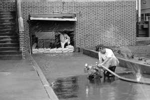 Workmen pump water from the first floor of an apartment building on Friday, Sept. 27, 1985, after Hurricane Gloria skirted Virginia Beach, Va., and headed northward.