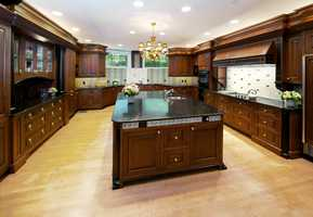 The home has a gourmet kitchen with top-of-the-line appliances and elegant mahogany paneled cabinetry.