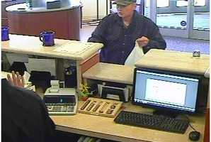 Police are searching for a man who violently robbed a Cambridge bank at gunpoint Tuesday morning.
