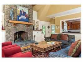 The family room is cozy and informal with a high beamed ceiling and lovely stone fireplace.