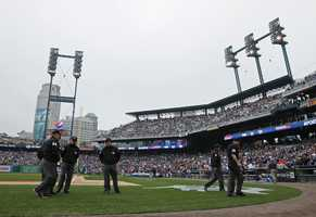 Umpires walk off the field as stadium lights go out at Comerica Park to delay the game in the second inning during Game 3 of the American League baseball championship series between the Boston Red Sox and the Detroit Tigers Tuesday, Oct. 15, 2013, in Detroit.