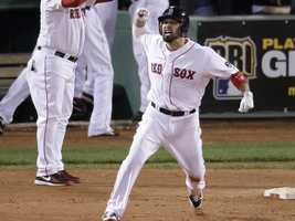 Boston Red Sox's Shane Victorino, front, celebrates his grand slam against the Detroit Tigers as he rounds first base in the seventh inning during Game 6 of the American League baseball championship series on Saturday, Oct. 19, 2013, in Boston.