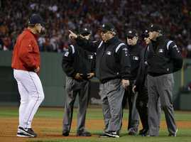 Umpire Joe West, pointing, talks to Boston Red Sox manager John Farrell after a long foul ball by Red Sox's Dustin Pedroia in the third inning.