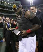 Boston Red Sox's David Ortiz celebrates with the championship trophy after the Red Sox beat the Detroit Tigers 5-2 in Game 6 of the American League baseball championship series on Saturday, Oct. 19, 2013, in Boston. The Red Sox advance to the World Series.
