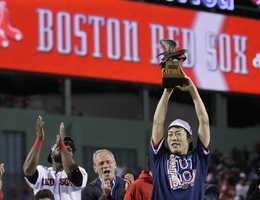 Boston Red Sox relief pitcher Koji Uehara hoists the most valuable player trophy after the Red Sox beat the Detroit Tigers 5-2 in Game 6 of the American League baseball championship series on Saturday, Oct. 19, 2013, in Boston. Uehara was named the series MVP, and the Red Sox advance to the World Series.