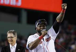 Boston Red Sox designated hitter David Ortiz, right, addresses the crowd alongside team owner John Henry, left, after the Red Sox beat the Detroit Tigers 5-2 in Game 6 of the American League baseball championship series on Saturday, Oct. 19, 2013, in Boston. The Red Sox advance to the World Series.