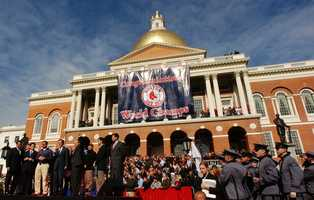 A banner is unveiled on the front of the Massachusetts Statehouse in Boston, Friday, Oct. 29, 2004, congratulating the Boston Red Sox as World Series champions. Gov. MItt Romney joined Boston Red Sox catcher Jason Varitek and World Series MVP Manny Ramirez at the noontime rally.
