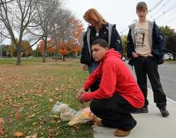 Christian Veatch, front, Gail Wade and Danvers High student Spencer Wade think about teacher Colleen Ritzer in front of the school at a make-shift memorial they have set up.