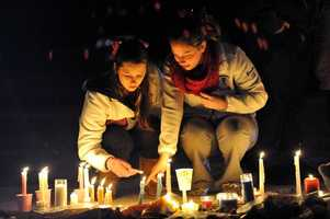Danvers High School students Emma Gamble, left, sophomore, and Brooke Baracewicz, right, junior, light a candle at a memorial outside the high school during a candle light vigil held for Danvers High School math teacher Colleen Ritzer who was murdered by one of her students, 14 year old Philip D. Chism.