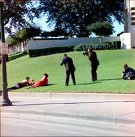Frightened onlookers lay on the grass in reaction to shots fired as cameramen record their actions at Dealey Plaza in Dallas, Texas, 22 November 1963.