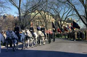 The funeral caisson carrying President Kennedy's casket enters the White House driveway, 25 November 1963. Honor guard horse riders, left to right: Richard Pace, James Stinton, and Charles Wade.