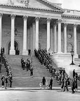 First Lady Jacqueline Kennedy, Caroline Kennedy, John F. Kennedy Jr., Robert F. Kennedy, Stephen Smith, Jean Kennedy Smith, and Secret Service Agent Cling Hill follow the casket up the stairs of the Capitol Building for the lying in state at the United States Capitol, 24 November 1963.