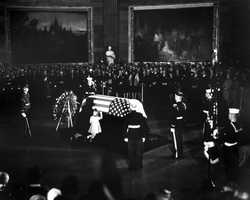 First Lady Jacqueline Kennedy and Caroline Kennedy kneel at the casket as the President's body lies in state in the Rotunda of the Capitol Building, 24 November 1963.