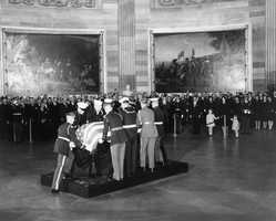 President Kennedy's body is placed in the Capitol Rotunda. The Kennedy family, Cabinet Secretaries, Administration Officials, and Members of Congress attend. 24 November 1963