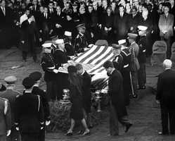 Burial ceremony for President Kennedy, lighting the Eternal Flame. Mrs. Jacqueline Kennedy, Attorney General Robert F. Kennedy, Senator Edward M. Kennedy, Honor Guard, mourners, foreign and U. S. dignitaries.