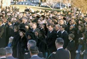 Members of the Kennedy family stand graveside during the burial service of President Kennedy, including Patricia Kennedy Lawford, Eunice Kennedy Shriver, Rose Fitzgerald Kennedy, Robert F. Kennedy, Jacqueline Kennedy, Peter Lawford, Edward M. Kennedy, Stan Radziwell, Stephen Smith, and Sargent Shriver. Arlington National Cemetery, Virginia, 25 November 1963.