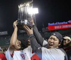 Boston Red Sox relief pitcher Koji Uehara, left, holds the championship trophy with teammate Junichi Tazawa after defeating the St. Louis Cardinals in Game 6 of baseball's World Series Wednesday, Oct. 30, 2013, in Boston. The Red Sox won 6-1 to win the series.
