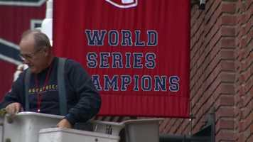 Workers used a bucket truck Thursday to put up the new championship banner along Yawkey Way.