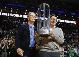 Boston Red Sox owner John Henry, left, and chairman Tom Werner hold the World Series trophy before an NBA basketball game between the Boston Celtics and the Milwaukee Bucks in Boston, Friday, Nov. 1, 2013.