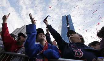 Boston Red Sox fans reach up for flying confetti during a parade in celebration of the baseball team's World Series win, Saturday, Nov. 2, 2013, in Boston.