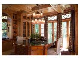 A handsome wood paneled study has floor to ceiling French doors that lead to a small covered terrace and overlook the homes well landscaped grounds.