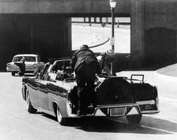 In this Nov. 22, 1963 file photo, President John F. Kennedy slumps down in the back seat of the Presidential limousine as it speeds along Elm Street toward the Stemmons Freeway overpass after being fatally shot in Dallas. Mrs. Jacqueline Kennedy leans over the president as Secret Service agent Clinton Hill rides on the back of the car.