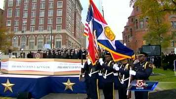 The honor guard begins the ceremony at Dealey Plaza in Dallas. The Texas School Book Depository where Lee Harvey Oswald fired the fatal shots is in the background.