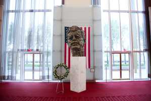 A memorial wreath stands next to the bronze memorial bust by Robert Berks of President John F. Kennedy in the grand foyer at the John F. Kennedy Center for the Performing Arts in Washington, Friday, Nov. 22, 2013, on the 50th anniversary of Kennedy's death.