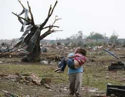A woman carries her child through a field near the collapsed Plaza Towers Elementary School in Moore, Okla., on May 20 following a massive tornado.