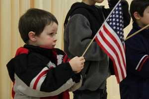 Tyler Moody of Danvers, Mass., holds an American flag as he and his brothers wait for the ceremonies to begin.