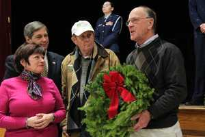 Boxford Selectman Peter Perkins accepts a wreath for the town as Merrill Worcester (c), Boxford Selectwoman Mary Anne Nay (l) and State Sen. Bruce Tarr look on.