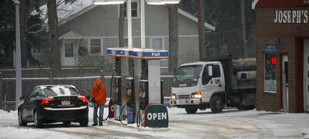The station attendant at Joesph's Garage on Main Street in Norwell Center fills a drivers tank with gas, many drivers top off during a snow storm to add weight to their cars.