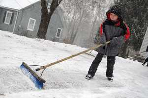 Nolen Rec, 8, of Brockton, helps clear his aunt's driveway in West Bridgewater during a snowstorm on Thursday, Jan. 2, 2014.