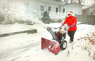 Lisa Julian, of Weymouth plows the driveway of her Lovell Street home, Thursday, Jan. 2, 2014.