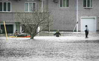 Sean Rielly, 18, a 6th Ave resident, kayaks as brothers Jack, 9 and Matt, 14 wade through the flood waters. A major nor'easter included heavy snowfall and coastal flooding in Scituate, Friday, Jan. 3, 2014.