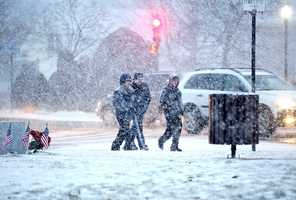 Pedestrians walk in heavy snow on Washington Street in Braintree near Town Hall. Snow began to fall around 4pm across the South Shore as a major winter storm was expected to hit the region, Tuesday, Jan 21, 2014.