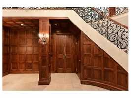 The grand foyer has a sweeping staircase and boxed wood walls.