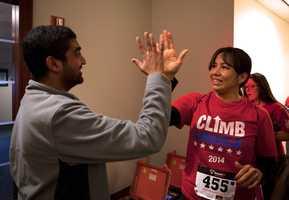 "Vinayak Sinha (left), a ""ClimbCorps"" member, gives Dina Martinez a high five when she arrives at the finish point."