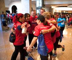 Team members hug each other after they finished the climbing. They raised $1,805 together.