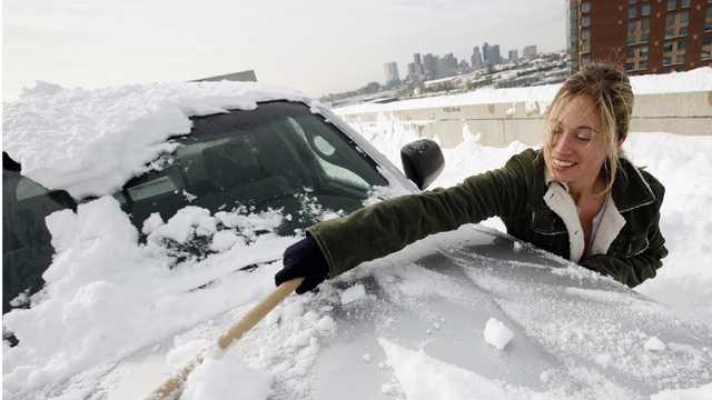 Snow woman scrapes car.jpg