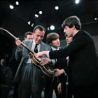 Paul shows his guitar to Ed Sullivan.