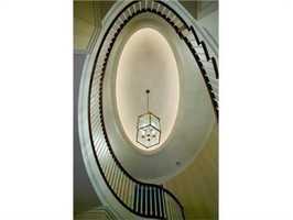 The gracious foyer showcases a custom elliptical staircase