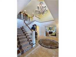 Gorgeous two story foyer with wainscot & marble inlay floor.