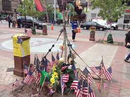American flags and other items left at the Copley Square Memorial for the 2013 Boston Marathon.