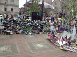 Running shoes, American flags and other items left at the Copley Square Memorial for the 2013 Boston Marathon