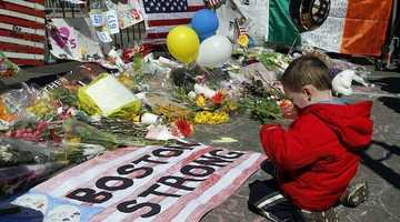 A young boy kneels in front of a section of the Marathon Memorial in Copley Square. Internet meme from a collection of Boston Marathon memes gathered by Elena Agapie.