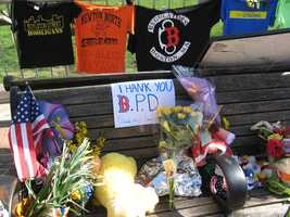 "Photograph of a bench at the Copley Square memorial covered in flowers, a sign reading ""Thank you B.P.D. (and all law enforcement),"" and Boston-themed T-shirts."
